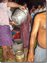 Pouring water to use in preparing the body