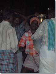 Villager dancing to the drums as people carry puja materials